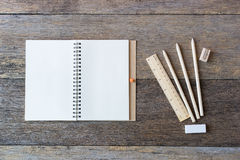 Open notebook on wooden background with pencils and ruler. Stock Photo
