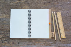 Open notebook on wooden background with pencils and ruler. Stock Photos