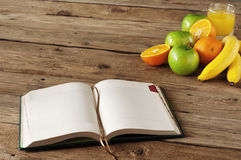 Open notebook on wooden table with fruits and orange juice Stock Image