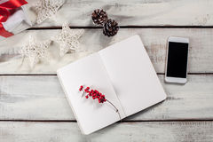 The open notebook on the wooden table with a phone Royalty Free Stock Photos