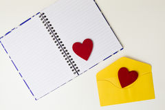 Open notebook, yellow envelope and two red felt hearts on white table. Top view. Copy space Stock Images