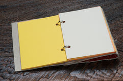 Open Notebook. With yellow page on wooden background Stock Photos