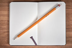 Open notebook and yellow pencil on a brown wooden table Stock Photo