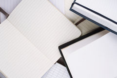 Open notebooks with white pages. Horizontal top view of many open notebooks in different shapes and sizes with white pages Royalty Free Stock Images
