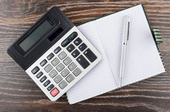 Open notepad, ballpoint pen and electronic calculator on table Royalty Free Stock Photo