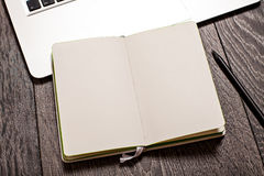 Open notepad with blank pages on table with laptop Stock Photos