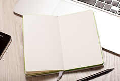 Open notepad with blank pages on table with laptop Stock Image