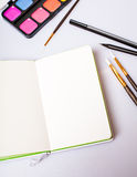 Open notepad with blank pages on table with office tools Royalty Free Stock Image