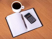 Open notepad, calculator and cup of coffee Royalty Free Stock Photo