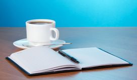 Open notepad, cup of coffee and saucer Stock Photo