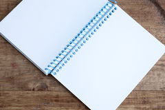Open notepad with empty pages laying on a wooden table Stock Photography