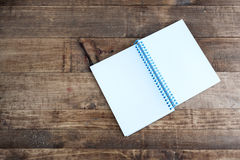 Open notepad with empty pages laying on a wooden table Royalty Free Stock Images