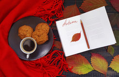 Open notepad with empty white pages and the inscription Autumn, a cup of coffee and cookies in a plate. Red warm scarf on wooden background with autumn leaves Stock Photography