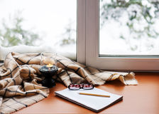 Open notepad, glasses, candle, pencil and beige warm plaid. Open notepad, glasses, candle, pencil and beige warm plaid located on stylized wooden windowsill Stock Photos