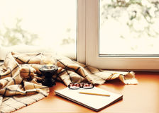 Open notepad, glasses, candle, pencil and beige warm plaid. Open notepad, glasses, candle, pencil and beige warm plaid located on stylized wooden windowsill Royalty Free Stock Image