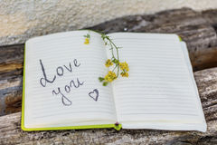 Open Notepad with love you sign. And yellow flower on a wooden background royalty free stock image