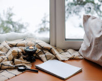 Open notepad, magnifier glass, pillow, candle and beige warm pla. Id located on stylized wooden windowsill. Winter concept of comfort and relaxation Royalty Free Stock Images