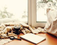 Open notepad, magnifier glass, pillow, candle and beige warm pla. Id located on stylized wooden windowsill. Winter concept of comfort and relaxation. Photo with Royalty Free Stock Photography