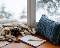 Open notepad, magnifier glass, pillow, candle, pencils and plaid. Open notepad, magnifier glass, pillow, candle, pencils and beige warm plaid located on stylized Stock Photography