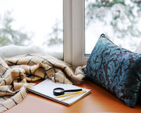 Open notepad, magnifier glass, pillow, pencils and beige warm pl. Aid located on stylized wooden windowsill. Winter concept of comfort and relaxation Stock Photo