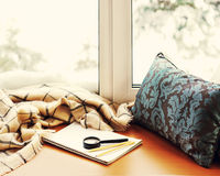 Open notepad, magnifier glass, pillow, pencils and beige warm pl. Aid located on stylized wooden windowsill. Winter concept of comfort and relaxation. Photo with Stock Images