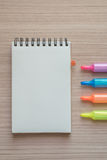 Open notepad with marker pens on wood Royalty Free Stock Photo