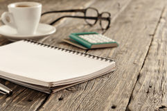 Open notepad with pen, cup of coffee, calculator and glasses Royalty Free Stock Photo