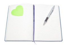 Open notepad with a pen and a green heart. Royalty Free Stock Photos