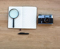 Open Notepad, pen, magnifying glass and camera Stock Photography