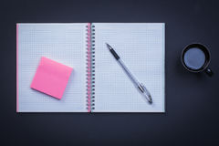 Open notepad pen sticky note and cup of coffee on Stock Photos