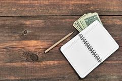 Open Notepad, Pencil And Dollars Cash On Rough Wood Background Royalty Free Stock Photos