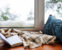 Open notepad, pillow, pencils and beige warm plaid located on s. Tylized wooden windowsill. Winter concept of comfort and relaxation Royalty Free Stock Images