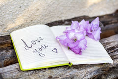 Open Notepad with pink gladiolus and love you sign Royalty Free Stock Photos