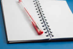 Open Notepad and red pen on a blue background, Stock Photo