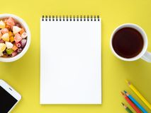 Open notepad on the spiral with a clean white page, a Cup with tea, caramels in a bowl, a smartphone and color pencil Stock Photography