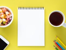 Open notepad on spiral with clean white page, cup with tea, caramels in a bowl, smartphone and color pencil Stock Images