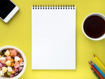 Open notepad on the spiral with a clean white page, a Cup with tea, caramels in a bowl, smartphone and crayon. On bright yellow background color Stock Photos