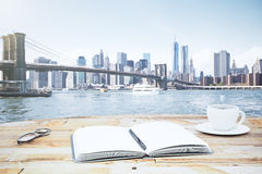 Open notepad on a wooden table with a a cup of coffee and a view. Of New York Stock Photography