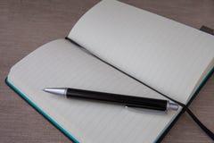 Open notitieboekje en zwarte pen stock foto