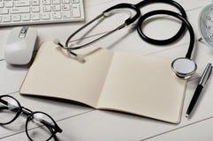 Open notitieboekje met blanco pagina's met een stethoscoop Stock Foto's