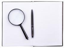 Open notitieboekje met een pen en een vergrootglas Stock Afbeeldingen