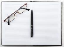 Open notitieboekje met een pen en glazen Stock Afbeelding