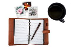 Open notitieboekje met een pen, paar van polaroidbeelden en een kop thee stock afbeelding