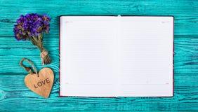 Open notitieboekje met lege pagina's en houten hart op een blauwe achtergrond De ruimte van het exemplaar Stock Afbeeldingen