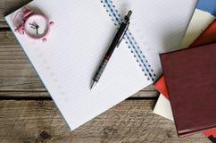 Open notitieboekjeagenda met tijdschema en bos van boeken met smal Royalty-vrije Stock Foto's