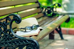 An open novel book, stylish glasses and a straw hat lie on a par. K bench Royalty Free Stock Photo