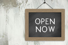 Open Now Sign. Blackboard hanging on the wall Royalty Free Stock Images