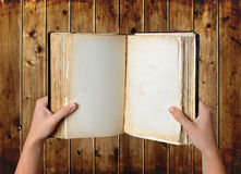 Open old blank book in hands Royalty Free Stock Photo