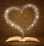 Open old book. A star, heart graphic at the top of the book Royalty Free Stock Photos