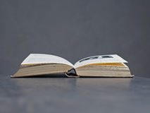 Open old book with beige canvas binding, soft grey background Royalty Free Stock Images